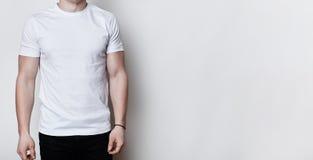 Ein Porträt eines Mannes, der den athletischen Körper trägt das leere weiße T-Shirt steht auf weißem Hintergrund mit Kopienraum f Stockbilder