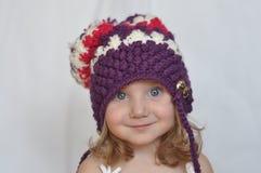 Ein Porträt eines netten Babys in einer violetten Kappe Stockfoto