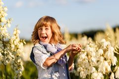 Ein Porträt eines netten kleinen Jungen mit blauen Augen und dem langen blonden Haar draußen auf dem Gebiet von den Blumen, die S stockbilder