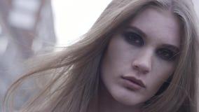 Ein Porträt eines schönen, herrlichen braunen behaarten Mädchens, das sinnlich zur Kamera auf unscharfem Stadthintergrund schaut  stock video