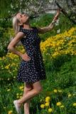 Ein Porträt eines schönen jungen Mädchens in einem blauen Kleid im Garten mit den Apfelbäumen, die Spaß und das Genießen habend b stockbild