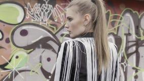 Ein Porträt eines sexy braunen behaarten Mädchens mit einem Pferdeschwanz, der stilvolle schwarze Jacke mit weißer langer Fransen stock video footage