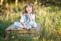 Ein Porträt eines traurigen kleinen Jungen mit blauen Augen und langen blonden dem Haar, die draußen auf einem Korb bei Sonnenunt stockbilder