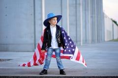 Ein Porträt von modernem, proude Junge, der amerikanische Flagge hält Lizenzfreies Stockbild