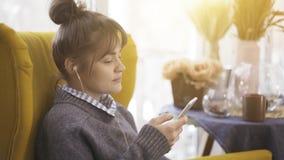 Ein Porträtprofil eines lächelnden Mädchens in den Kopfhörern, die ein Telefon halten stockbilder