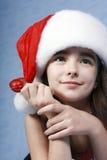 Ein Portrait des Mädchens ist in der Weihnachtsschutzkappe. Stockfoto