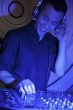 Ein Porträt eines jungen Mannes DJ, der Musik in einem Nachtklub spielt Lizenzfreie Stockfotografie