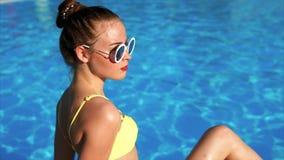 Ein Profil einer jungen Frau, die durch das Pool und die sunbaths in einem Badeanzug sitzt stock footage