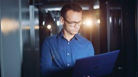 Ein Programmierer geht in einen Serverraum mit einem Laptop in den Händen, Abschluss oben stock video