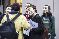 Ein Protestierender, der eine Guy Fawkes-Maske trägt, hält ein Plakat stockfotos