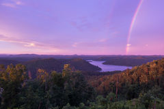 Ein Purpur farbiger Himmel mit einem Regenbogen bei Sonnenuntergang über Mountainsee lizenzfreies stockfoto
