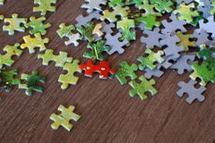 Ein Puzzlespiel mit grünen Teilen und einem roten Detail zerstreute auf den Bretterboden Stockfotografie