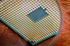 Ein quadratischer Computerprozessor zog von einem defekten Computer Der Prozessor ist auf dem Tisch Ansicht der Kontakte durch ei lizenzfreies stockbild