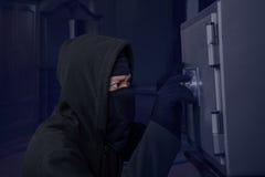Ein Räuber, der versucht, einen Sicherheitskasten zu öffnen Lizenzfreies Stockfoto