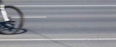 Ein Rad eines Fahrrades auf der Fahrbahn Hintergrund des Asphalts Stockfotos