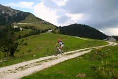 Ein Radfahrer auf der Straße zwischen den Feldern mit Ansicht über die Berge und den Häusern in den Wolken Lizenzfreie Stockfotos