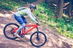 Ein Radfahrer in einem Sturzhelm steigt vom Berg auf einem orange Fahrrad ab Lizenzfreies Stockfoto