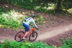 Ein Radfahrer in einem Sturzhelm steigt vom Berg auf einem orange Fahrrad ab Lizenzfreies Stockbild