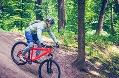 Ein Radfahrer in einem Sturzhelm steigt vom Berg auf einem orange Fahrrad ab Lizenzfreie Stockfotos