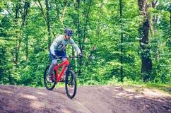 Ein Radfahrer in einem Sturzhelm steigt vom Berg auf einem orange Fahrrad ab Stockfotografie