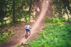 Ein Radfahrer in einem Sturzhelm steigt vom Berg auf einem orange Fahrrad ab Stockfotos