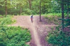 Ein Radfahrer in einem Sturzhelm steigt vom Berg auf einem orange Fahrrad ab Stockfoto