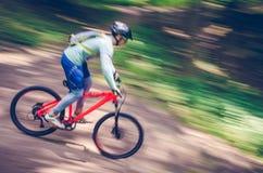 Ein Radfahrer in einem Sturzhelm steigt vom Berg auf einem orange Fahrrad, Bewegungsunschärfe ab Stockbild