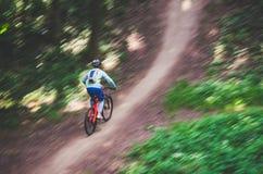 Ein Radfahrer in einem Sturzhelm steigt vom Berg auf einem orange Fahrrad, Bewegungsunschärfe ab Lizenzfreie Stockfotos