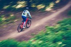 Ein Radfahrer in einem Sturzhelm steigt vom Berg auf einem orange Fahrrad, Bewegungsunschärfe ab Lizenzfreies Stockbild