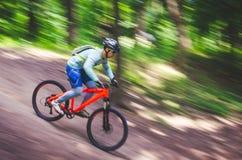 Ein Radfahrer in einem Sturzhelm steigt vom Berg auf einem orange Fahrrad, Bewegungsunschärfe ab Stockbilder