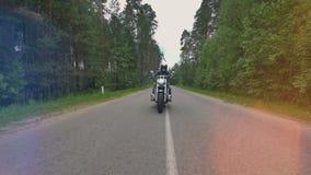 Ein Radfahrer in einer Schädelmaske fährt auf die Straße, die durch Bäume umgeben wird 4K stock video footage