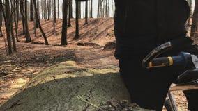 Ein Radfahrer stoppt, um sein smartwatch zu überprüfen, das in den Blättern steht, bedeckte forrest stock video