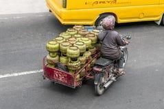 Ein Radfahrer transportiert die Gasflaschen auf verkehrsreicher Straße in Sumatra stockfoto