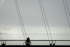 Ein Radfahrerreiten auf einer Schrägseilbrücke Lizenzfreies Stockfoto