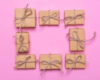 Ein Rahmen von den Geschenkboxen eingewickelt im Kraftpapier auf einem rosa Hintergrund Flaches Lagedesign, Draufsicht Lizenzfreies Stockfoto
