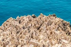 Ein rauer strukturierter Felsen durch das blaue adriatische Meer Stockfotografie