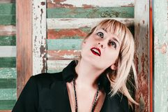 Ein recht blondes Mädchen im schwarzen Kleid lächelt playfully Lizenzfreie Stockfotografie