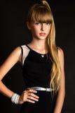Ein recht junges Mädchen auf dem schwarzen Hintergrund Stockbild