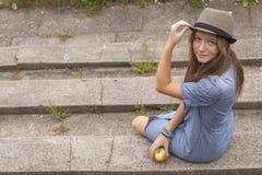 Ein recht junges Mädchen, das auf den Schritten im Stadt Park sitzt weg Stockfotos