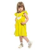 Ein recht kleines Mädchen in einem gelben Kleid Stockfoto