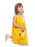 Ein recht kleines Mädchen in einem gelben Kleid Stockfotografie