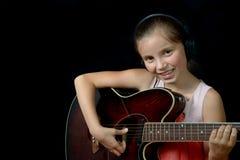 Ein recht kleines Mädchen, das Gitarre spielt Lizenzfreies Stockbild
