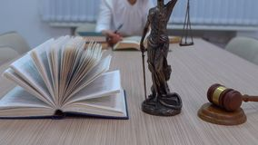 Ein Rechtsanwalt an dem Arbeitsplatz überprüft Dokumente und Gesetzgebung, die Statuette von Themis mit einem Rahmenplan stock video footage
