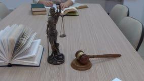 Ein Rechtsanwalt an dem Arbeitsplatz überprüft Dokumente und Gesetzgebung, die Statuette von Themis mit einem Rahmenplan stock video
