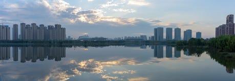 Ein reflektierender Abend des Panoramas geschossen von den Bäumen und von den Gebäuden stockfoto