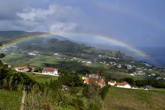 Ein Regenbogen, der über einem grünen Feld in das Meer auf der faial Insel sich ausbreitet Stockfotos