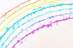 Ein Regenbogen, der mit einem dünnen Stift gezeichnet wird, verbreitet im Wasser stockfoto