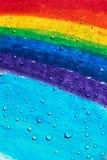 Ein Regenbogen gezeichnet mit den Zeichenstiften und Regentropfen, die auf ihn fallen stockfotografie