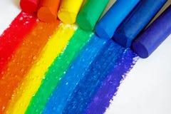Ein Regenbogen gezeichnet mit den Zeichenstiften und Regentropfen, die auf ihn fallen stockfotos