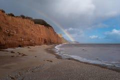 Ein Regenbogen setzt auf einem verlassenen Sidmouth-Strand in Devon, England auf stockbild